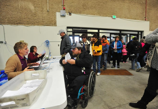 Elections workers assist Cascade County residents seeking to vote on Nov. 6 at Exhibition Hall at Montana ExpoPark.