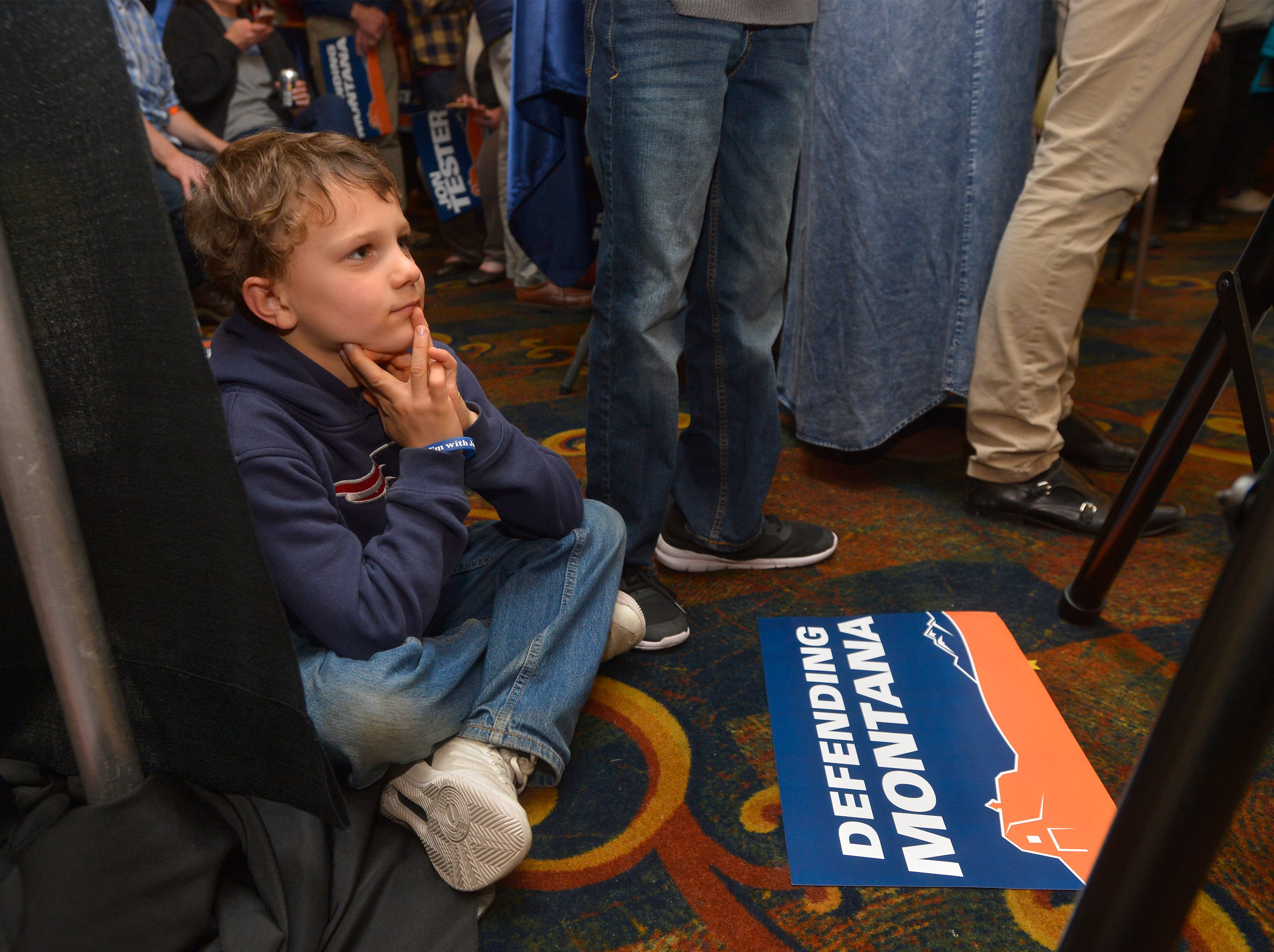 Tucker Schultz looks on as his grandfather, Senator Jon Tester, addresses his supporters late Tuesday evening during his election night party on at the Holiday Inn in Great Falls.