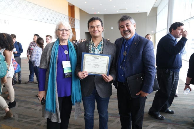 "University of Guam biology student Jordan Barcinas, center, won the ""Outstanding Research Presentation"" award at the Society for Advancement of Chicanos/Hispanics & Native Americans in Science (SACNAS) National Conference for his presentation on jellyfish. Standing with Barcinas are SACNAS Past President Dr. Maggie Werner Washburne, left, and SACNAS President Dr. Lino Gonzalez."