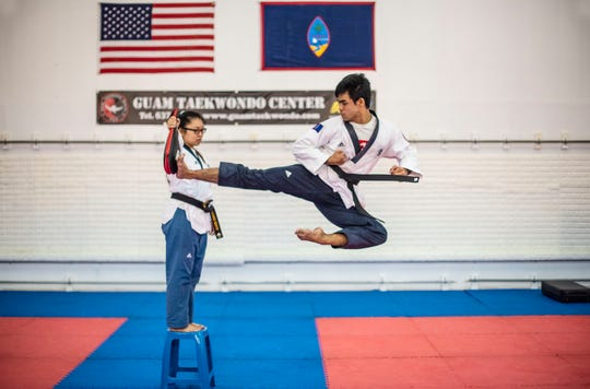 Second degree Taekwondo black belt Ryan Gaza practices the flying side kick, while Charisse Palaganas holds the target mitt. The flying side kick is a specialized kind of technique, which requires a martial artist to execute a side kick in mid-air hitting the target with the bladed part of the foot, or the heel after a running start. The seventh annual flying side kick tournament was held November 4 and was part of Guam Taekwondo Center's ongoing 16th anniversary celebration.