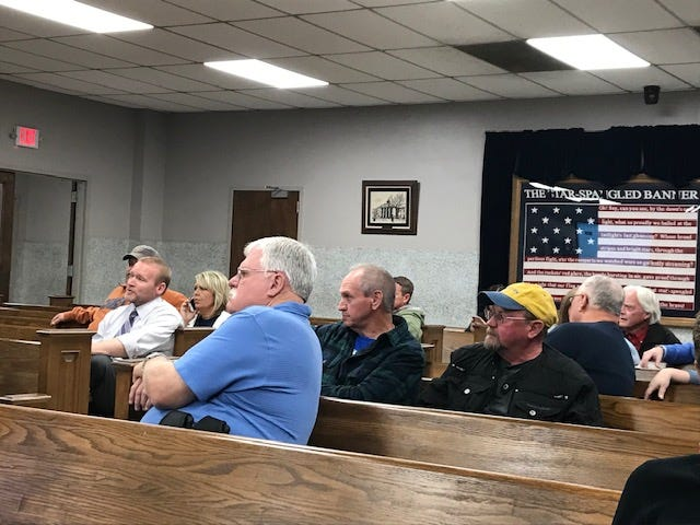 Coroner Bruce Farmer, Henderson City Commissioner Brad Staton and others watch as election results come in at the Henderson County Courthouse Tuesday night.