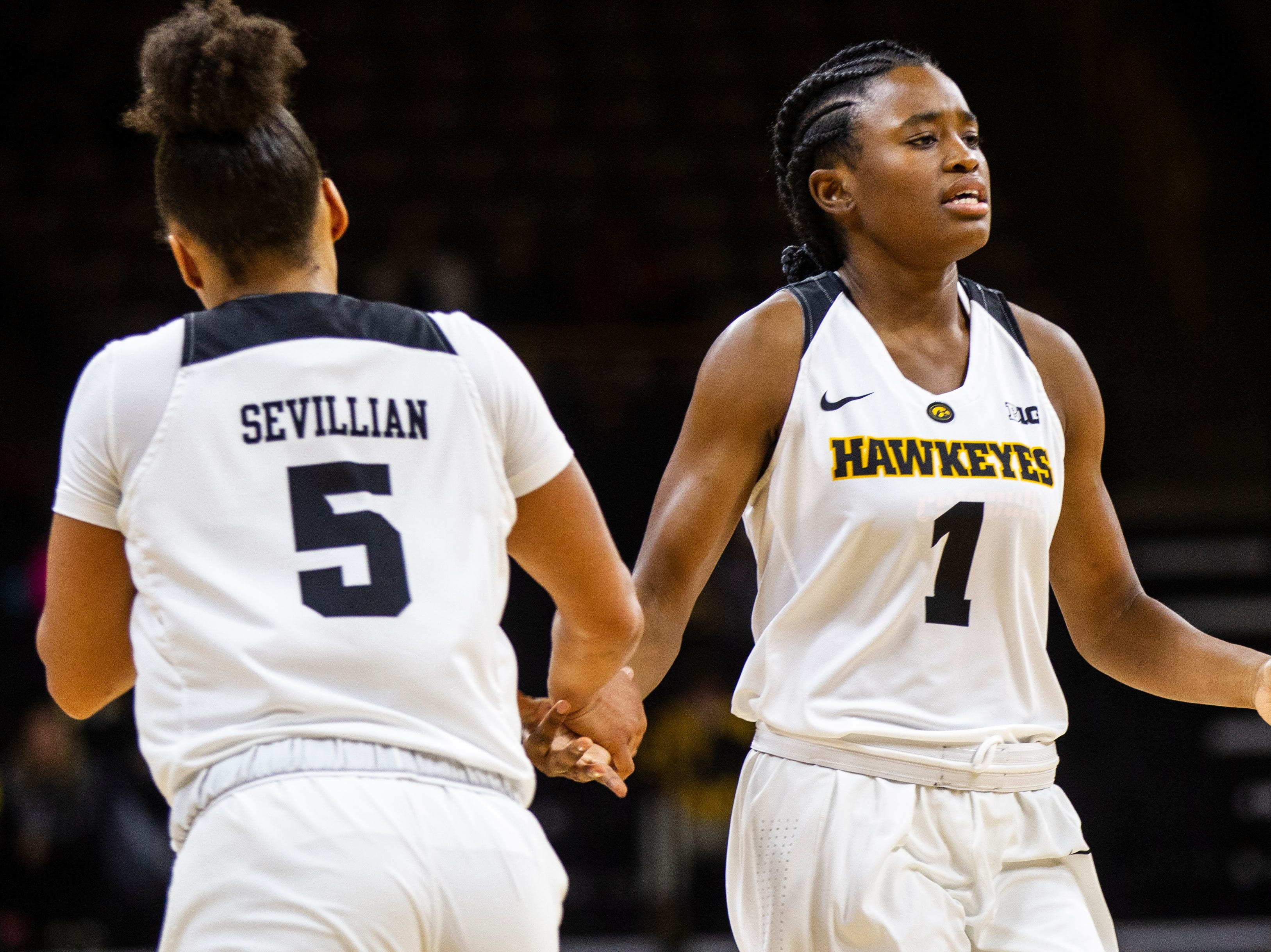 Iowa guard Tomi Taiwo (1) high-fives Iowa guard Alexis Sevillian (5) on her way into the game during a women's basketball exhibition basketball game on Tuesday, Nov. 6, 2018, at Carver-Hawkeye Arena in Iowa City.