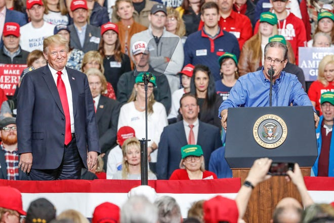 United States President Donald Trump listens as Republican senatorial candidate Mike Braun speaks during a rally at Southport Fieldhouse on Friday, Nov. 2, 2018.