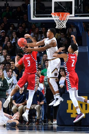 Notre Dame Fighting Irish forward Elijah Burns (12) reaches for a rebound between Illinois-Chicago Flames forward Jacob Wiley (3) and forward Michael Diggins (2) in the first half at the Purcell Pavilion.