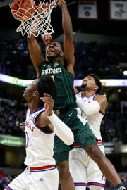 Michigan State forward Aaron Henry, center, dunks between Kansas defenders Marcus Garrett, left, and Dedric Lawson during the first half of an NCAA college basketball game at the Champions Classic in Indianapolis on Tuesday, Nov. 6, 2018.