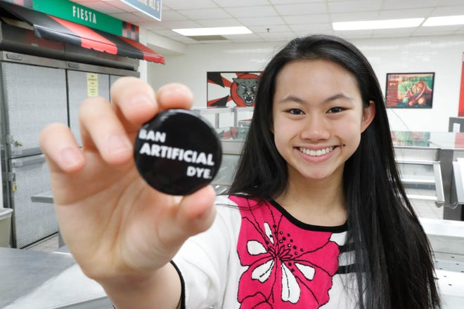 """North Central High School student, Grace Lee, holds one of her project buttons which reads """"Ban Artificial Dye"""" at North Central High School in Indianapolis on Wednesday, Nov. 7, 2018. School staffers worked with Lee to identify school foods which contain artificial dye after Lee developed carpal tunnel at an oddly young age, possibly due to eating yellow dye. Alternative medicine has linked artificial coloring to the wrist pain in people who have an allergy."""