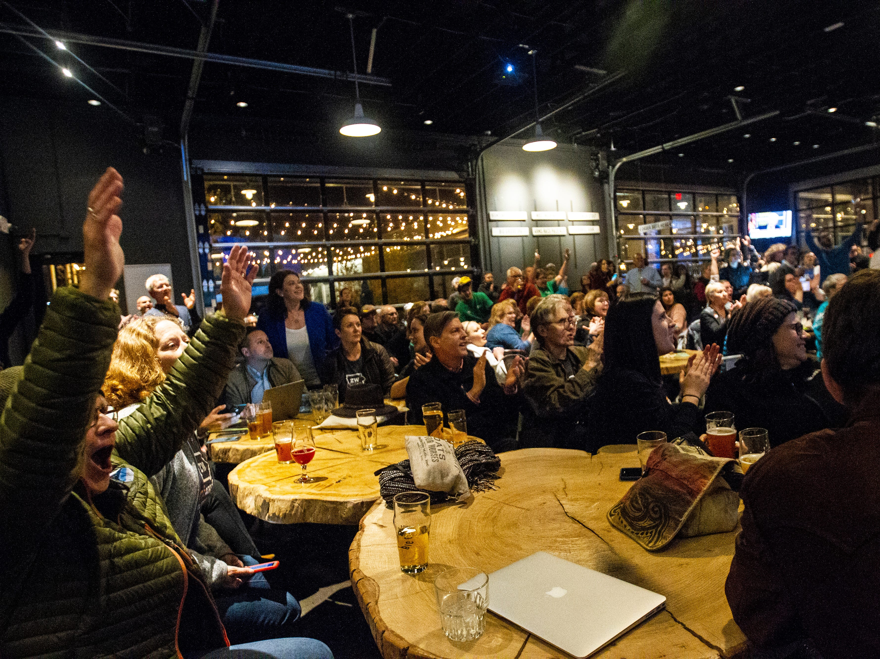 Johnson County Democrats cheer as results come in during their party on Tuesday, Nov. 6, 2018, at Big Grove Brewery in Iowa City.