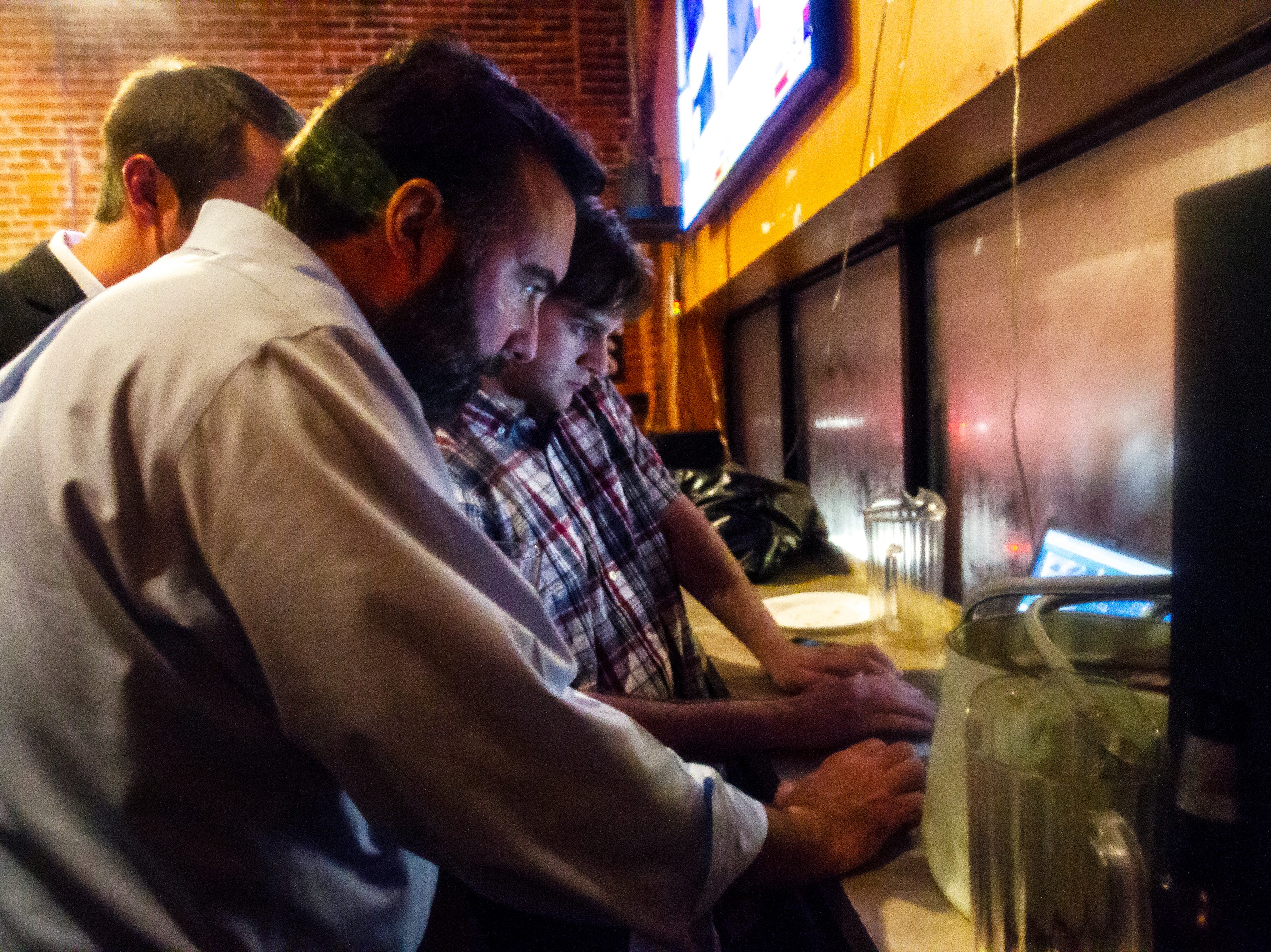 Christopher Peters checks election results during his watch party on Tuesday, Nov. 6, 2018, at the Airliner in Iowa City.