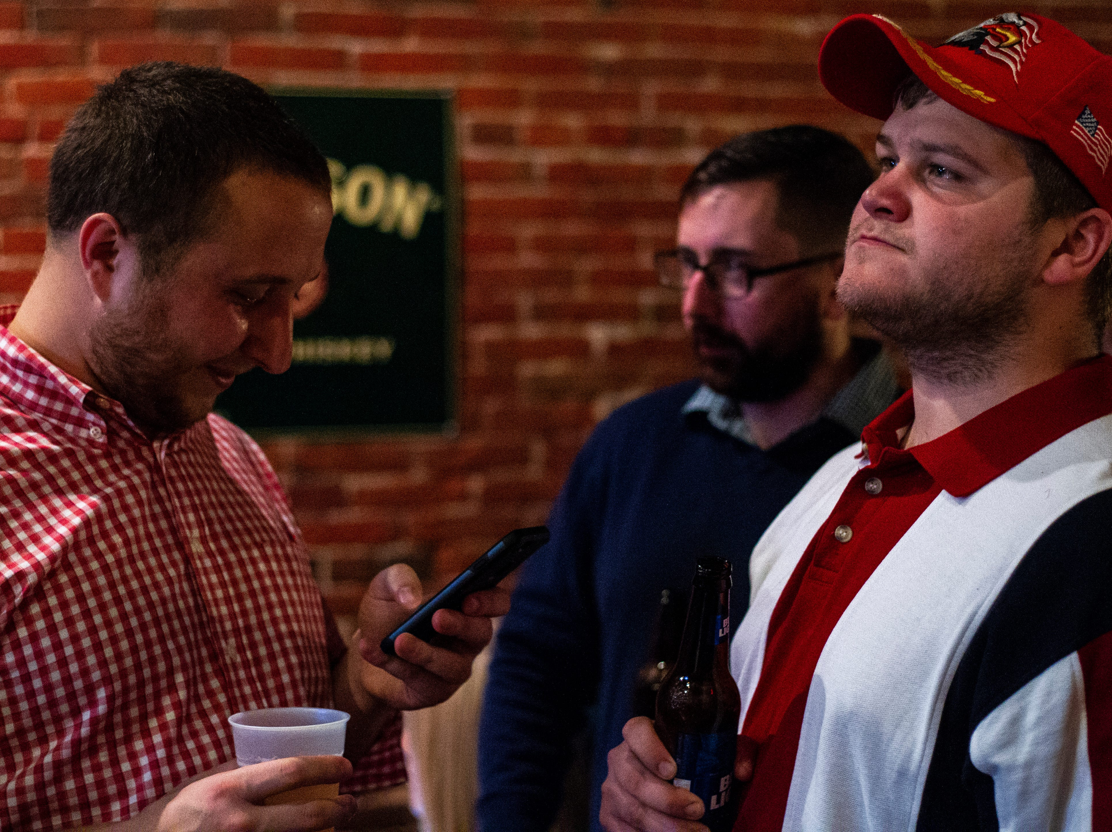 Patrick Wronkiewicz (left) checks election results during a watch party on Tuesday, Nov. 6, 2018, at the Airliner in Iowa City.