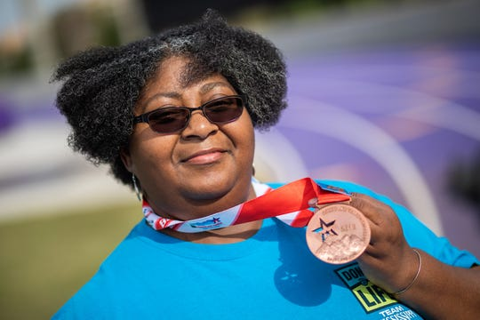Mo Crozier, a UMMC volunteer and heart transplant recipient, shows off the bronze medal she won in the corn hole competition at the Transplant Games. She is pictured at the Millsaps College track.
