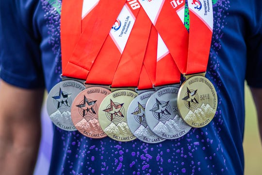 Timothy Lewis has a double handful of gold, silver and bronze medals that he won in the 2016 and 2018 Transplant Games of America.