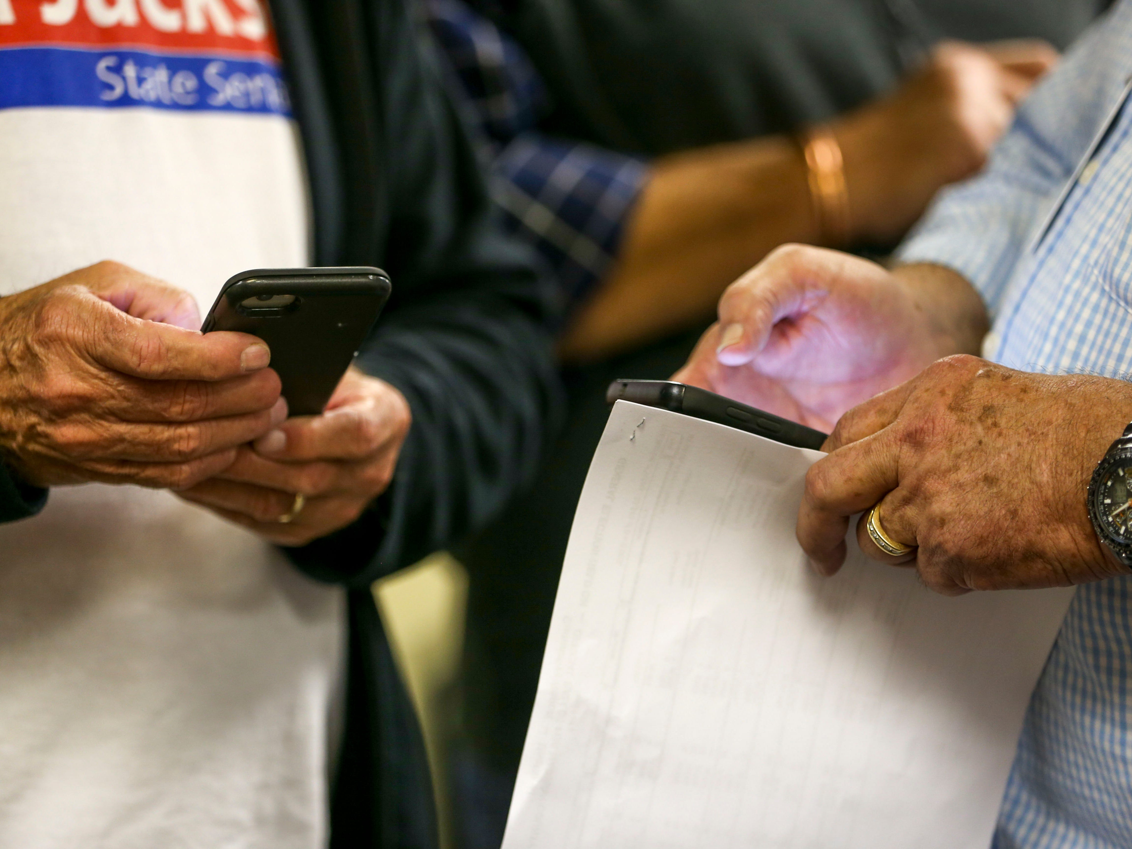 Attendees check their cell phones for election result coverage during an election night watch party at Madison County Republican Headquarters in Jackson, Tenn., on Tuesday, Nov. 6, 2018.