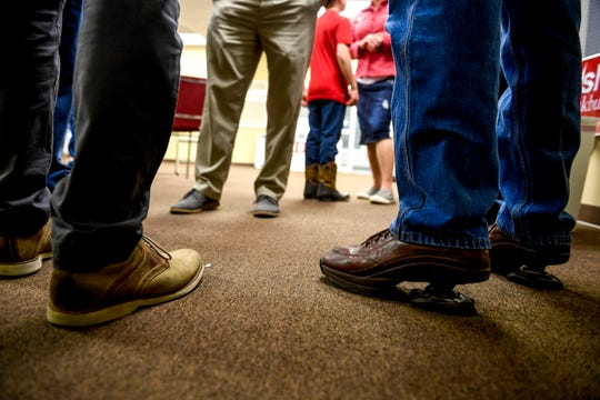 Attendees speak with Chris Todd, state Representative for District 73, left, wearing special shoes with springs under his heels, during an election night watch party at Madison County Republican Headquarters in Jackson, Tenn., on Tuesday, Nov. 6, 2018.