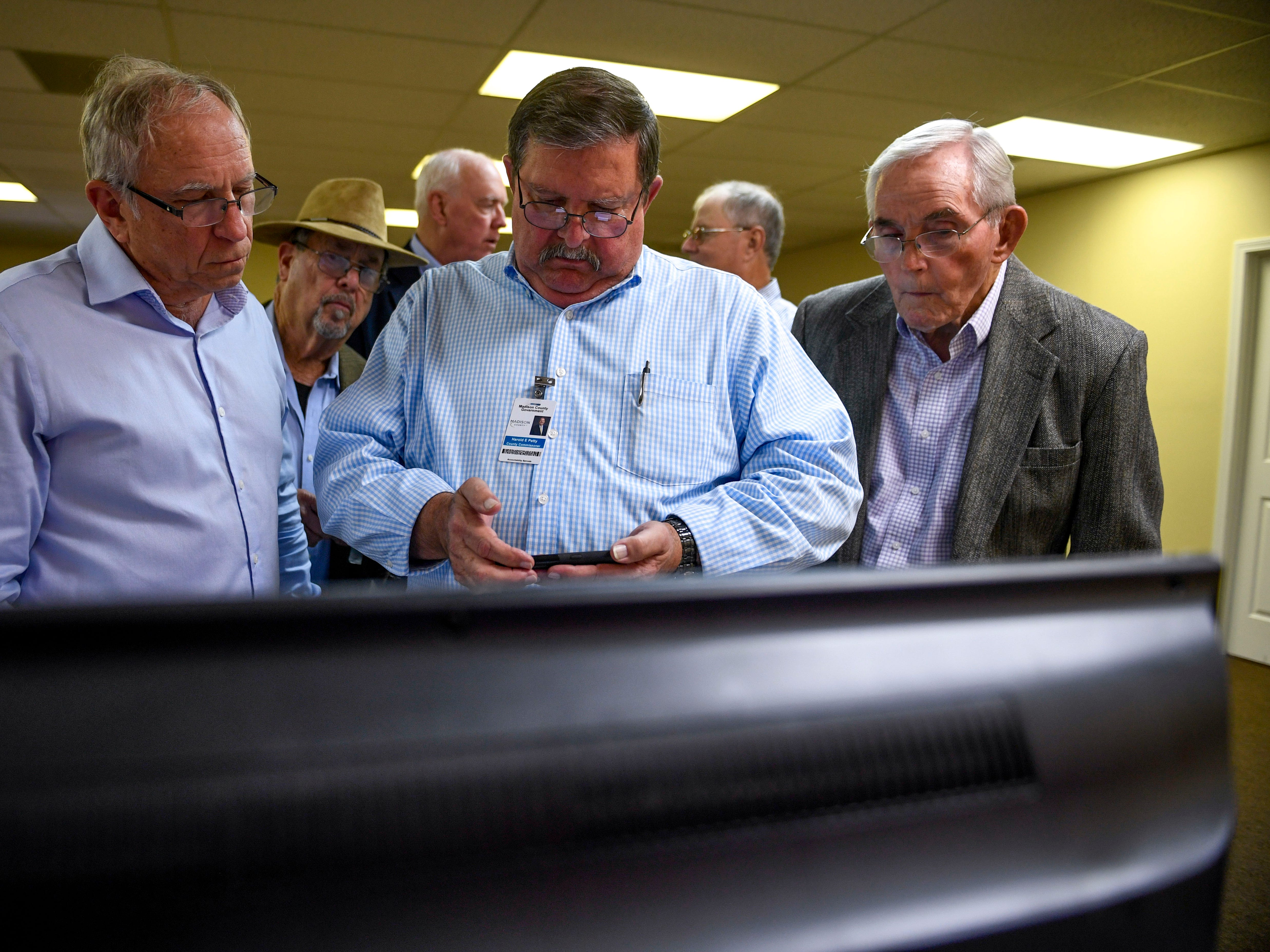 Attendees use their phones to track live election results while watching local television coverage during an election night watch party at Madison County Republican Headquarters in Jackson, Tenn., on Tuesday, Nov. 6, 2018.