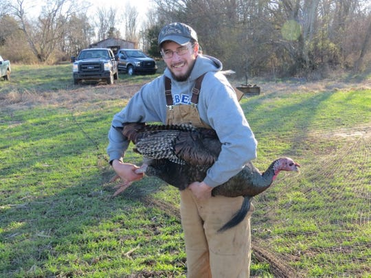 Vinnie Johnson, UT researcher, stands with a turkey he caught.