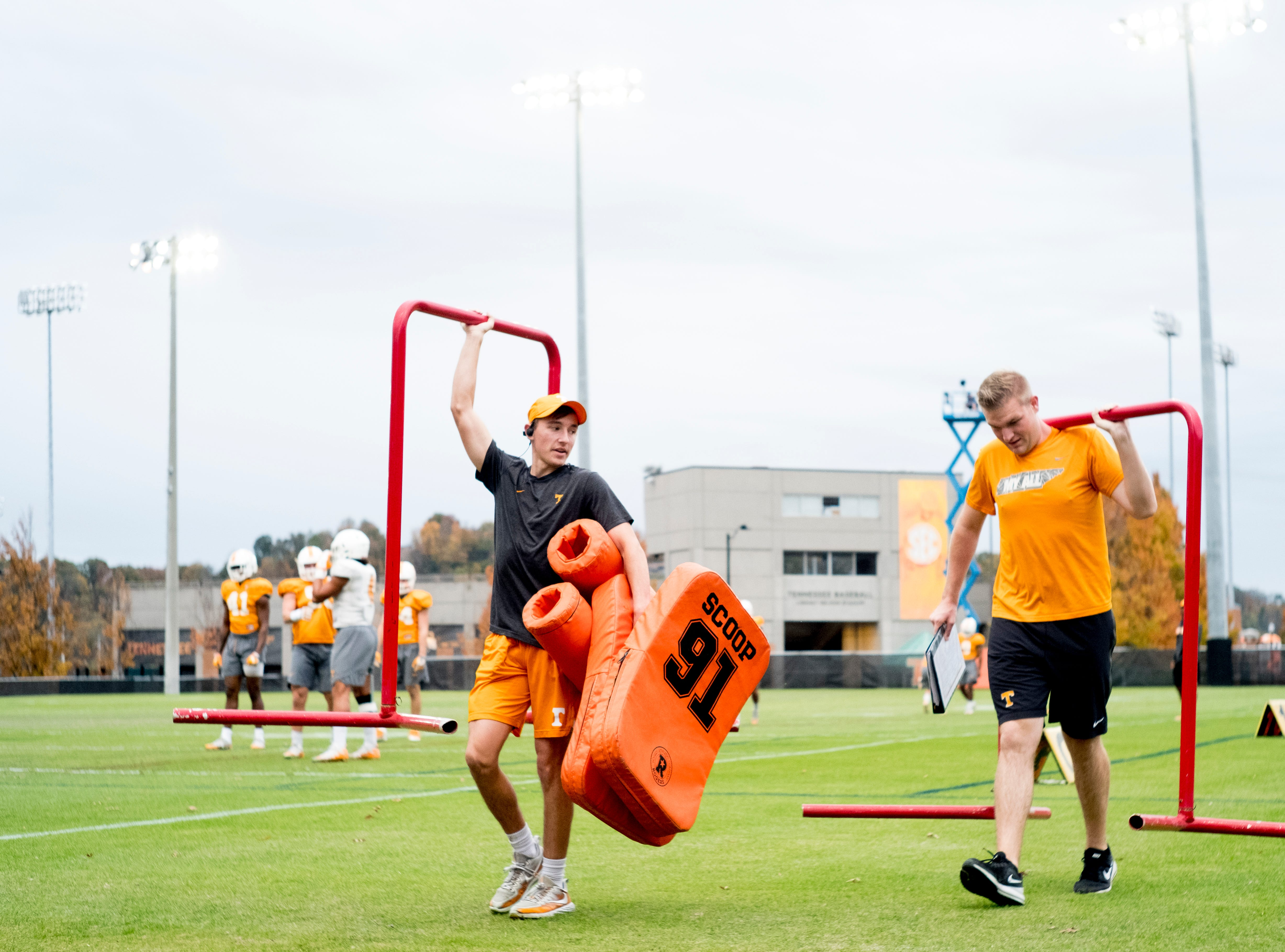 Team members carry equipment from the field during Tennessee fall football practice at Haslam Field in Knoxville, Tennessee on Wednesday, November 7, 2018.