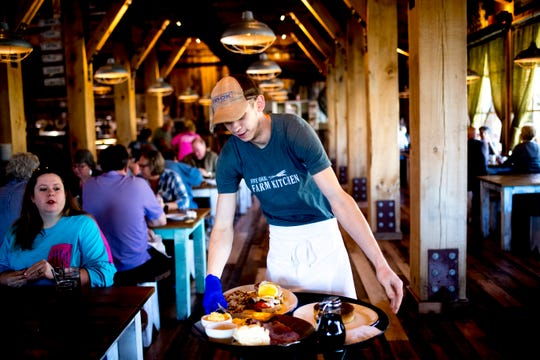 Server Tyler Daymen buses a table at Five Oaks Farm Kitchen, 1638 Parkway, in Sevierville, Tennessee on Wednesday, November 7, 2018. The new 17,000-square-foot restaurant, which serves Southern farm-style dishes, opened on land held by the Ogle family since the early 1900s.