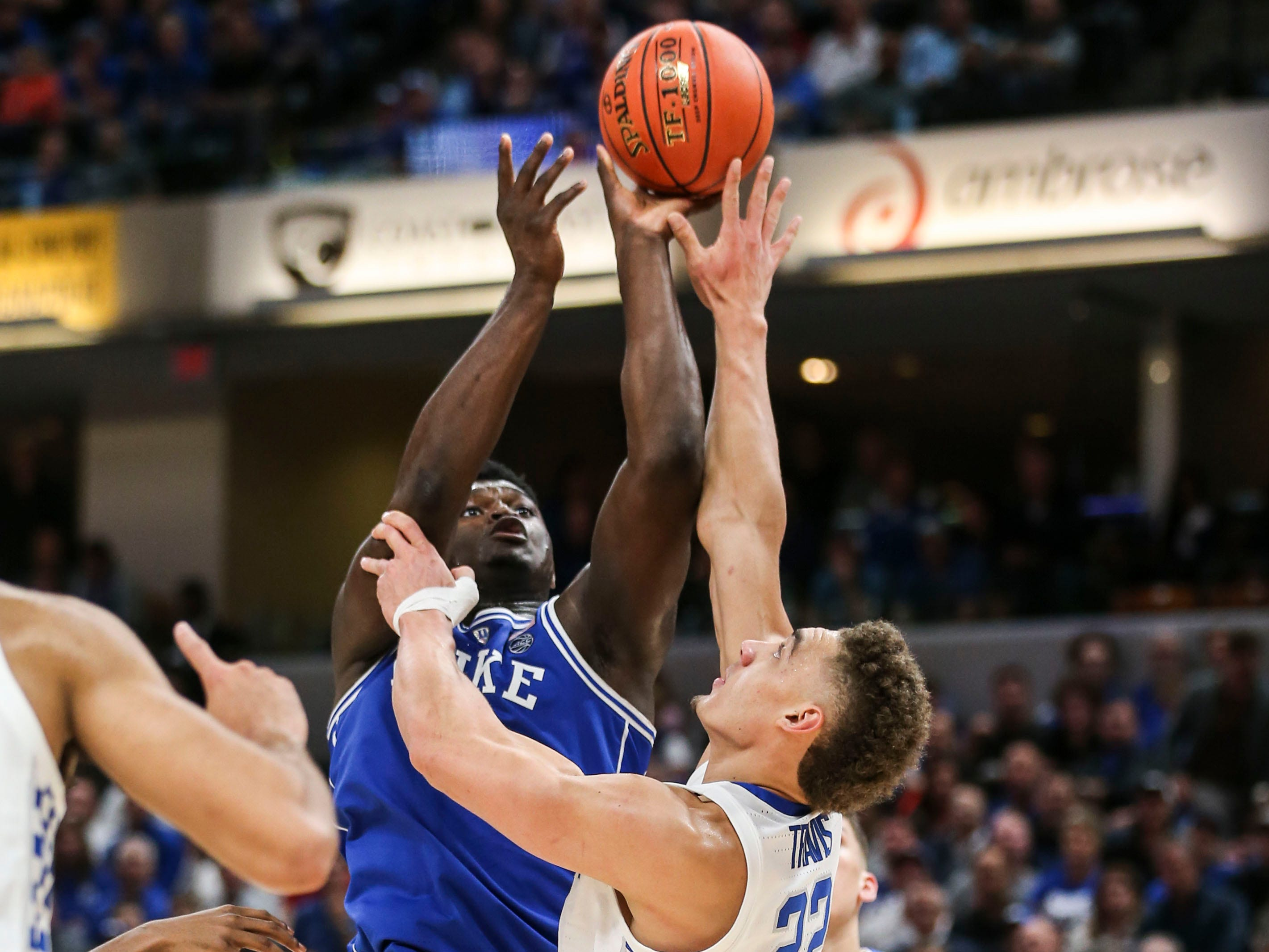Duke's Zion Williamson scores two of his  28 points over Kentucky's Reid Travis as the Blue Devils cruised past Kentucky 118-84 in the Champions Classic Tuesday night. Nov. 6, 2018