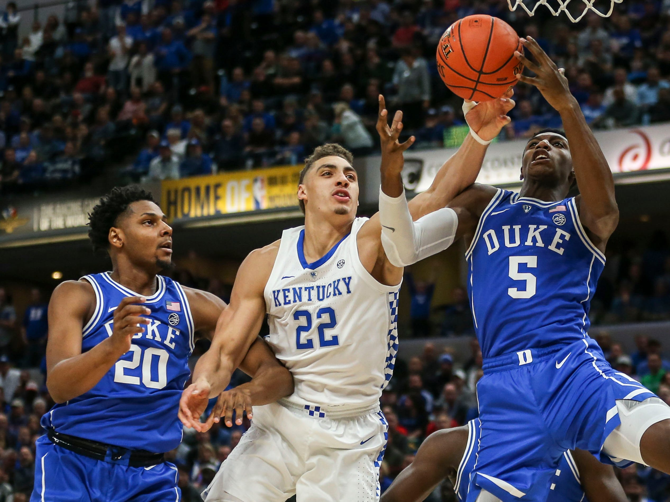 Kentucky's Reid Travis battles Duke's R.K. Barrett, right, and Marques Bolden for a rebound as the Blue Devils cruised past Kentucky 118-84 in the Champions Classic Tuesday night. Nov. 6, 2018