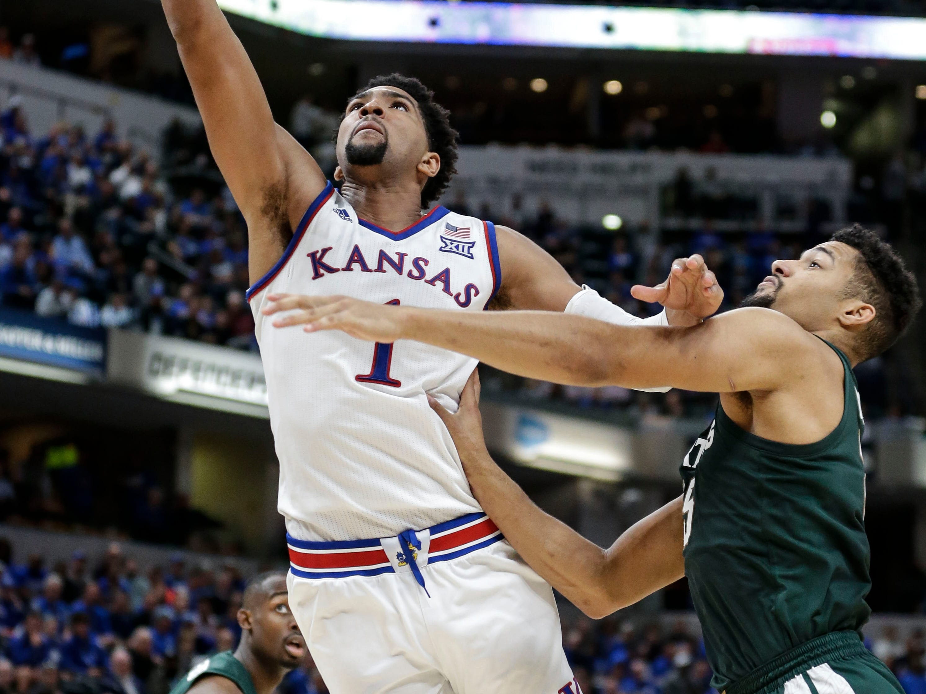 Kansas forward Dedric Lawson, left, shoots in front of Michigan State forward Kenny Goins during the second half of an NCAA college basketball game at the Champions Classic in Indianapolis on Tuesday, Nov. 6, 2018. Kansas won 92-87.