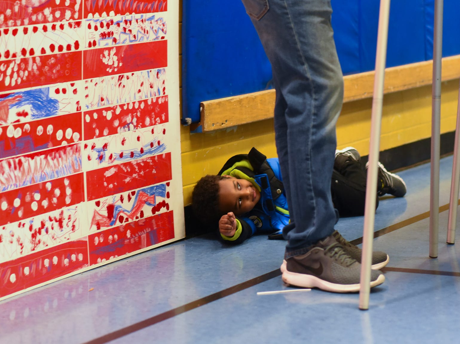 Two-year-old Abdallah Bussuri hangs out on the gymnasium floor at Willow School in Lansing while his father Adnan casts his ballot, Tuesday evening, Nov. 6, 2018, during the midterm election.