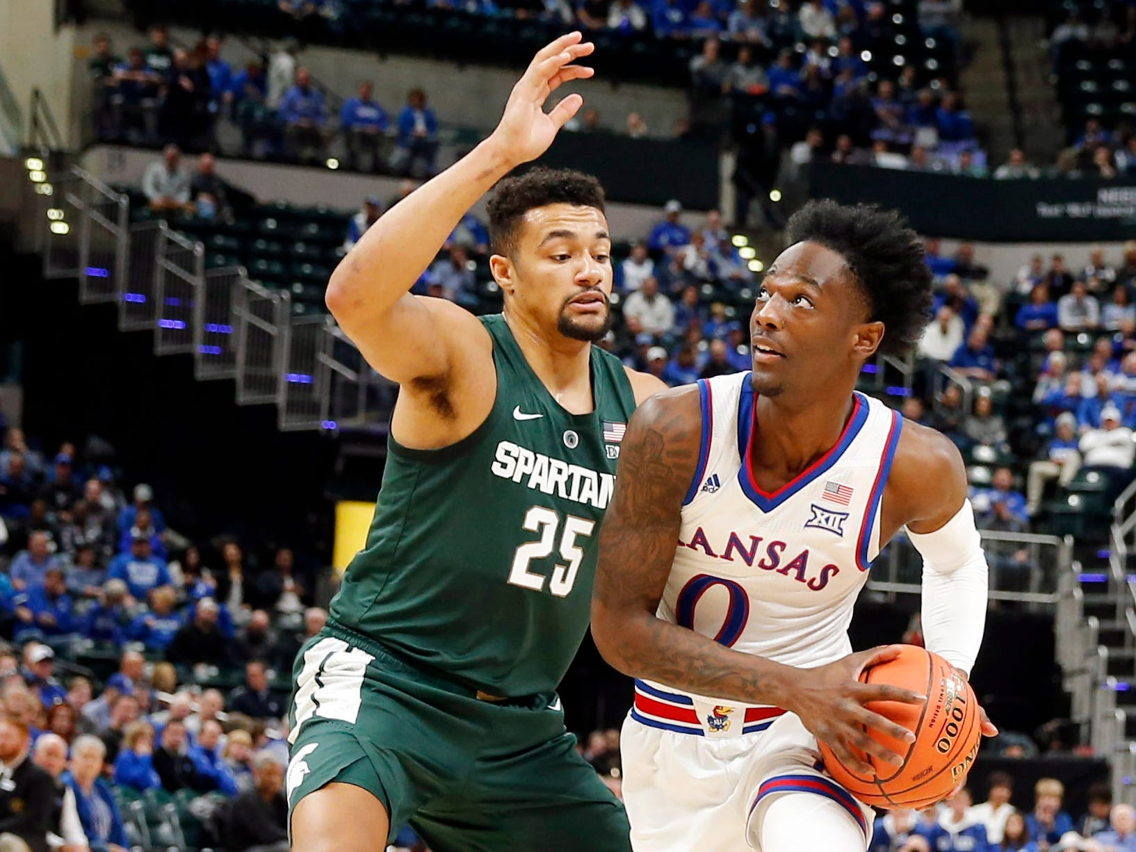 Kansas Jayhawks guard Marcus Garrett (0) drives to the basket against Michigan State Spartans forward Kenny Goins (25) in the first half during the Champions Classic at Bankers Life Fieldhouse.