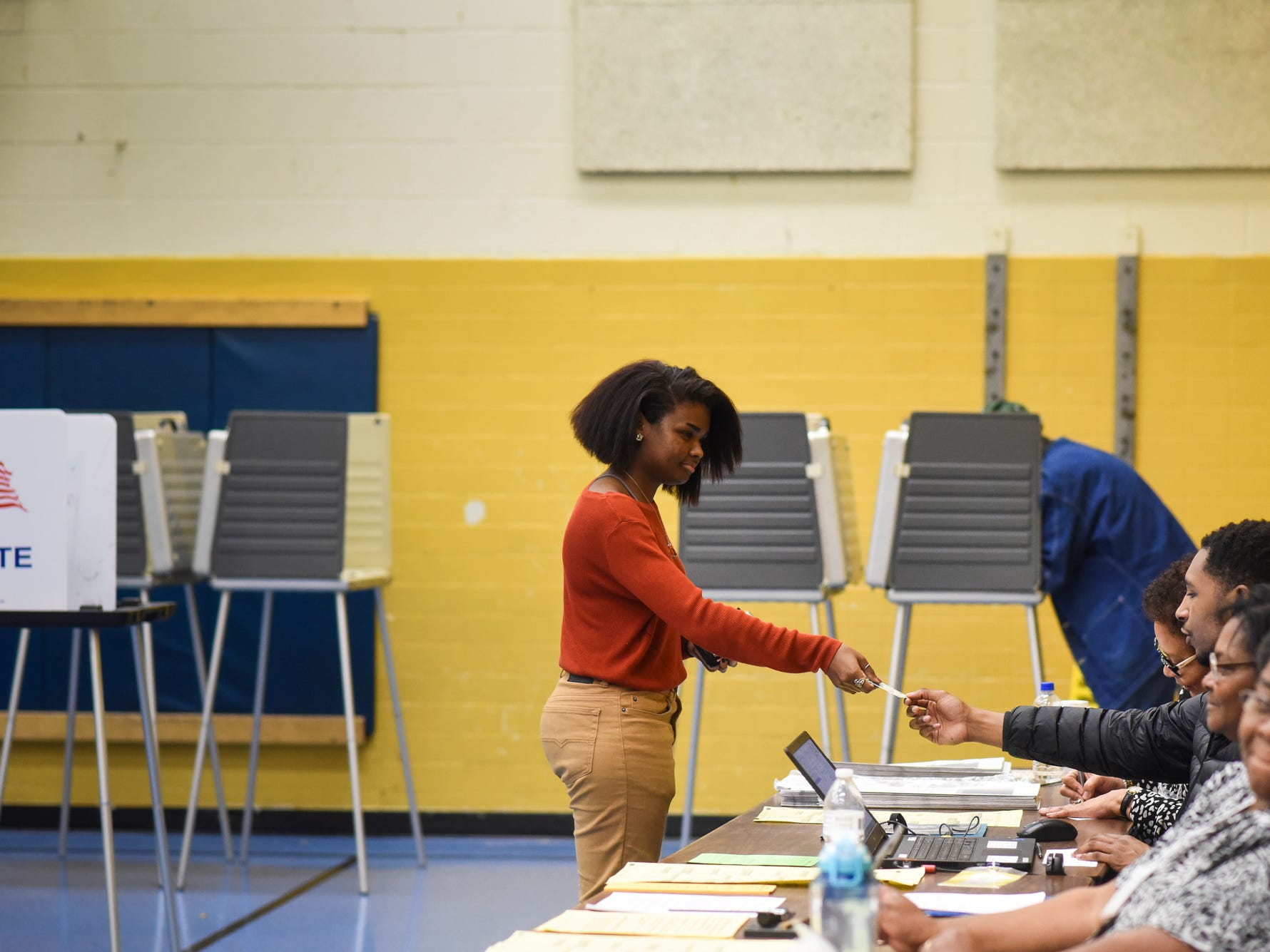 Thalia Wells, 19, of Lansing, hands her ID to an election official Tuesday evening, Nov. 6, 2018, at Willow School in Lansing.  It is her first time voting, and said Proposal One is her primary reason for voting.