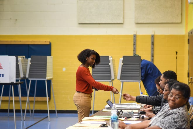 Thalia Wells, 19, of Lansing, hands her ID to an election official Tuesday evening, Nov. 6, 2018, at Willow School in Lansing. The May 7 election is the first in which same-day registration and no-reason absentee voting will be allowed in Michigan.