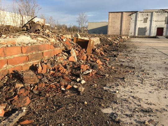 The remains of this brick wall and the concrete slab outline of the footprint of the former Lansing Sugar Co. warehouse.