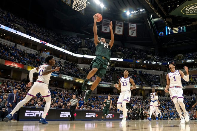 Michigan State forward Xavier Tillman (23) goes to the basket in front of Kansas defenders Marcus Garrett (0), David McCormack (33) and Dedric Lawson (1) during the first half of an NCAA college basketball game at the Champions Classic in Indianapolis on Tuesday, Nov. 6, 2018.