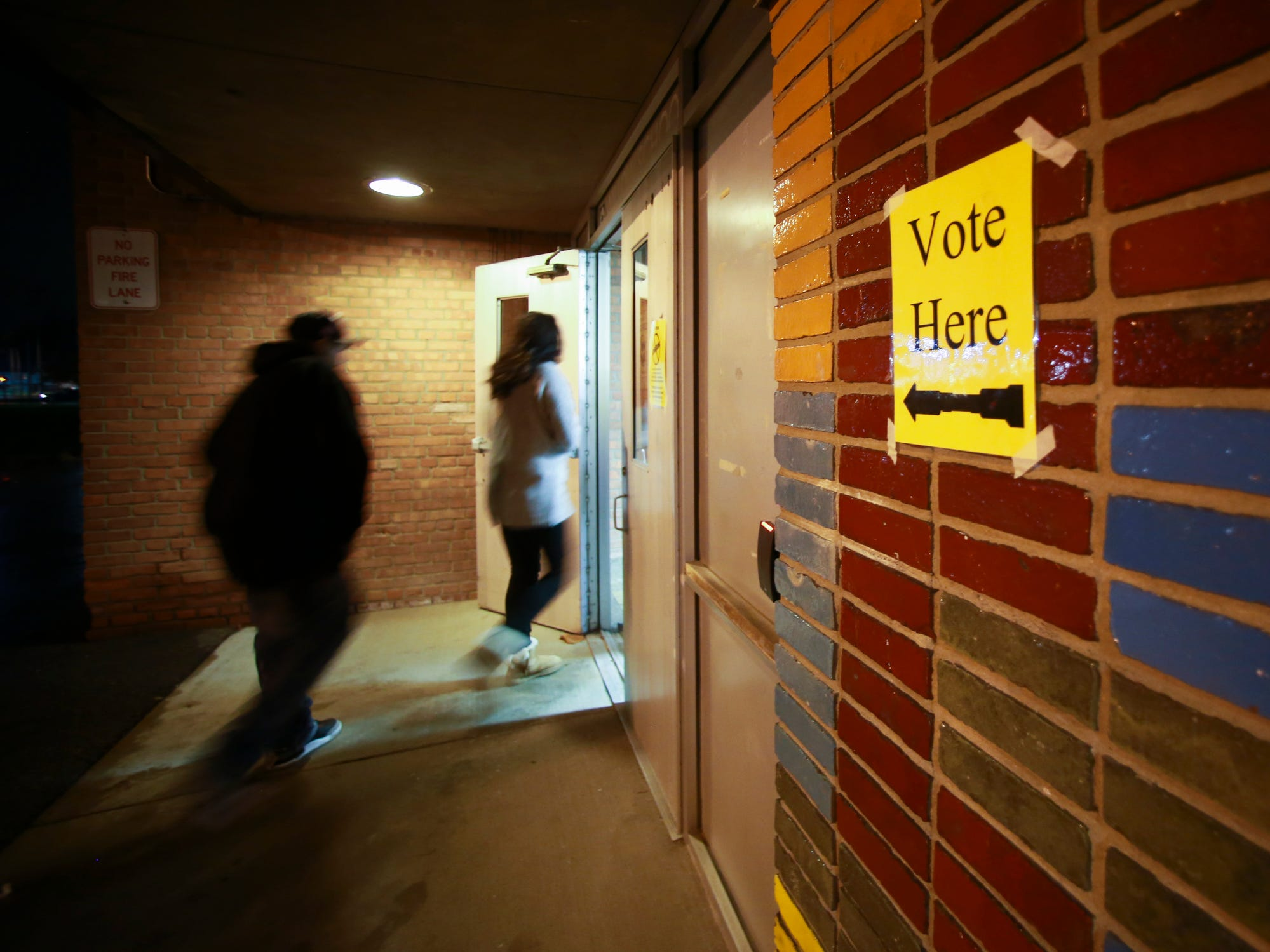 Last minute voters head into Willow School in Lansing Tuesday evening, Nov. 6, 2018, to cast their ballots in the 2018 midterm election.