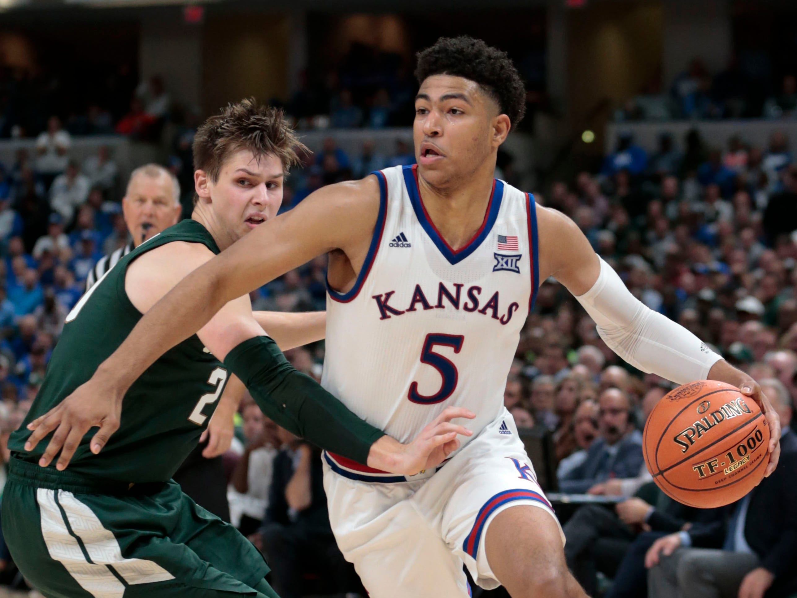 Kansas guard Quentin Grimes (5) goes around Michigan State guard Matt McQuaid (20) in the second half of an NCAA college basketball game at the Champions Classic in Indianapolis on Tuesday, Nov. 6, 2018. Kansas won 92-87.