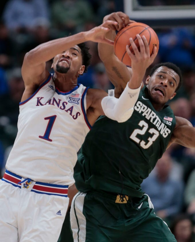 Kansas forward Dedric Lawson (1) fights for a rebound with Michigan State forward Xavier Tillman (23) during the first half of an NCAA college basketball game at the Champions Classic in Indianapolis on Tuesday, Nov. 6, 2018.