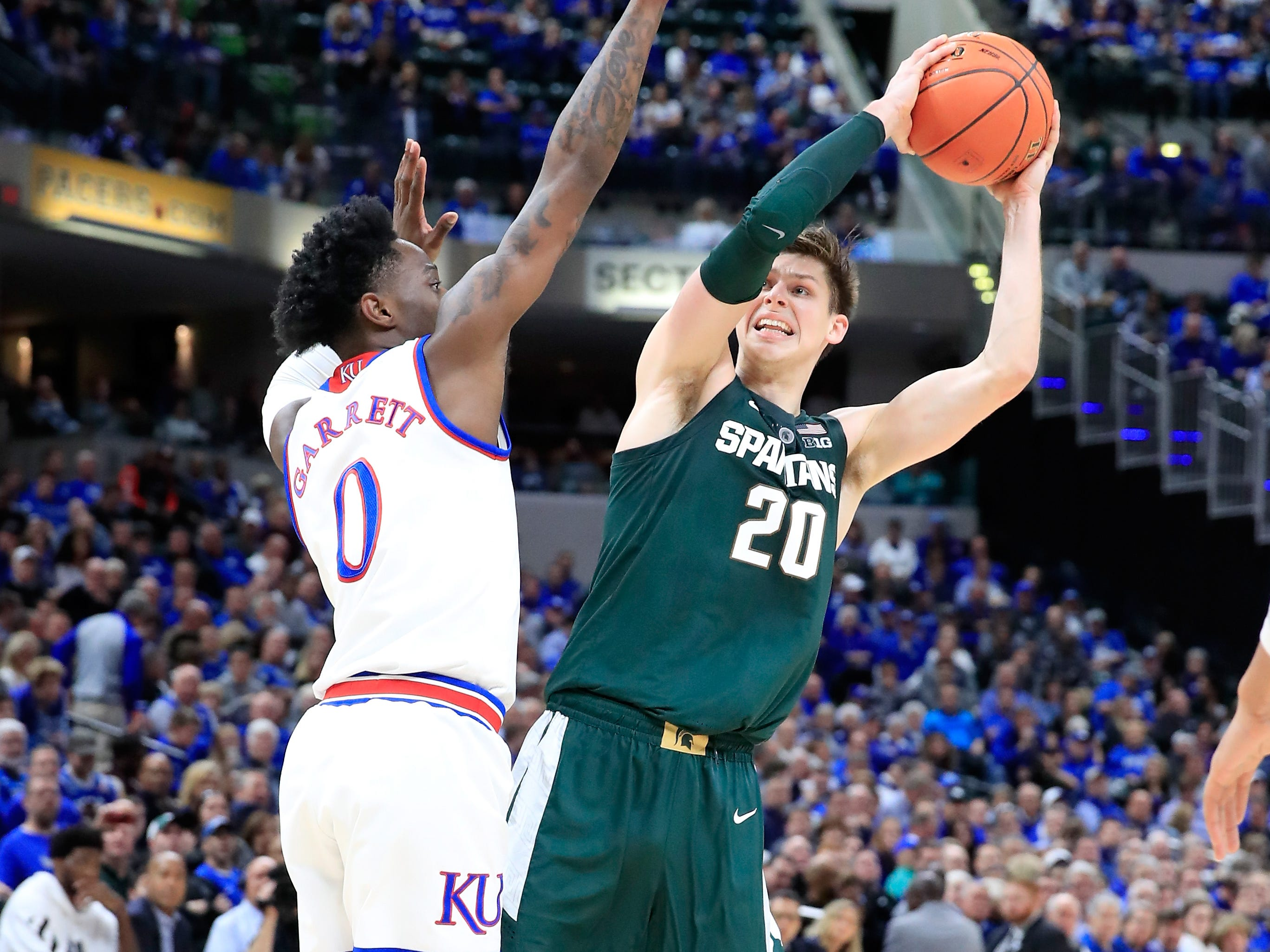 Matt McQuaid #20 of the Michigan State Spartans shoots the ball against the Kansas Jayhwaks during the State Farm Champions Classic at Bankers Life Fieldhouse on November 6, 2018 in Indianapolis, Indiana.