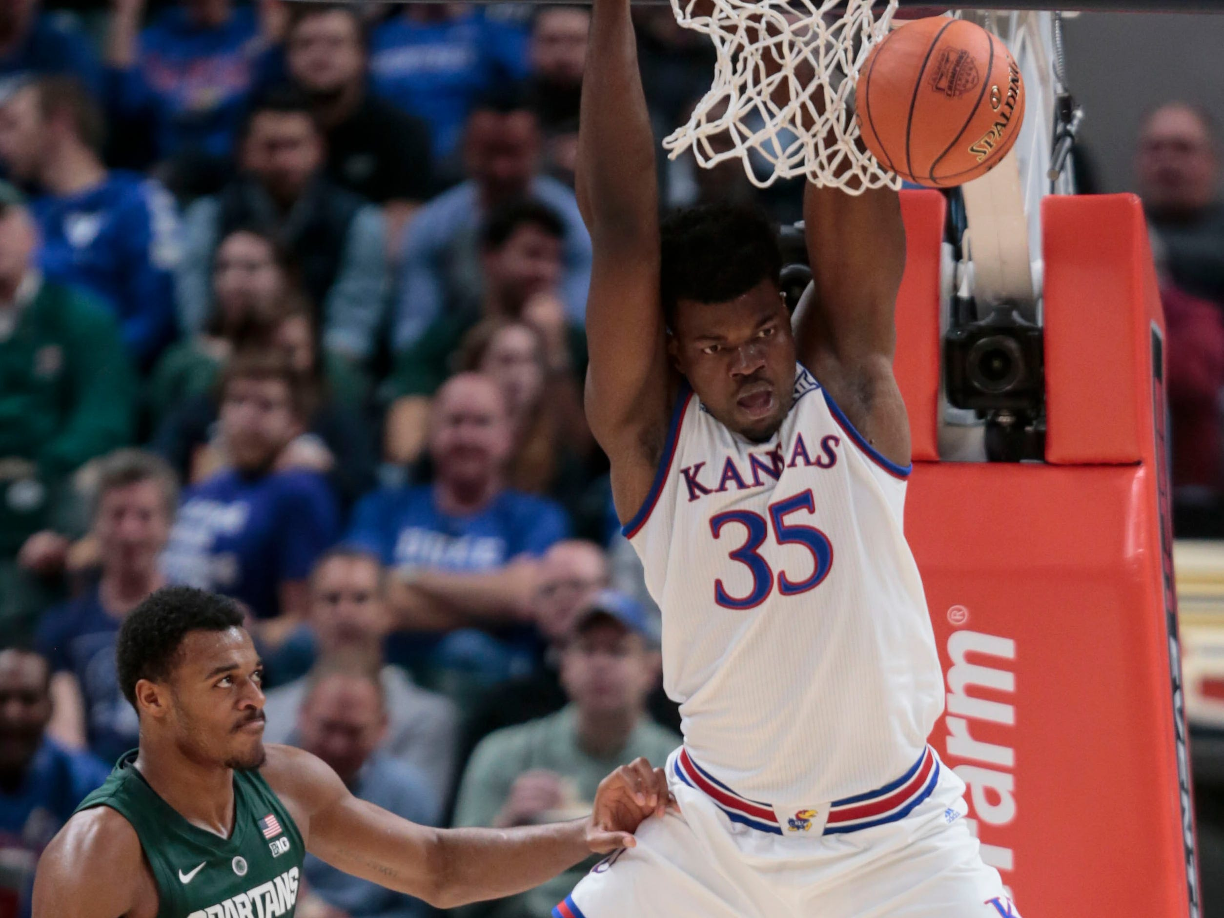 Kansas center Udoka Azubuike (35) dunks in front of Michigan State forward Xavier Tillman during the first half of an NCAA college basketball game at the Champions Classic in Indianapolis on Tuesday, Nov. 6, 2018.
