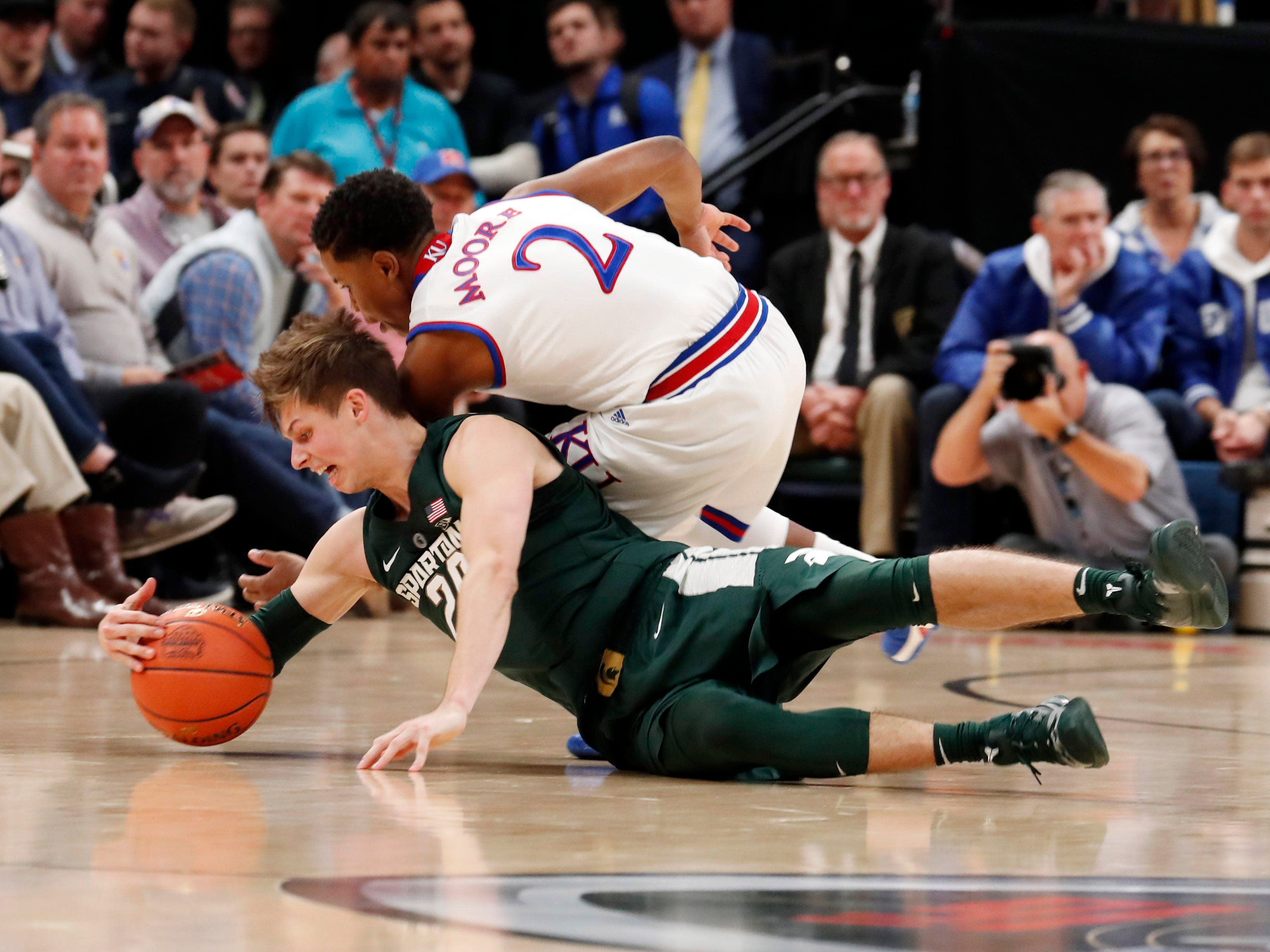Michigan State Spartans guard Matt McQuaid (20) scrambles for a loose ball against Kansas Jayhawks guard Charlie Moore (2) in the first half during the Champions Classic at Bankers Life Fieldhouse.