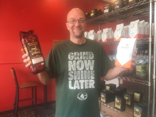 JT Dachtler shows a couple of the different brands of coffee you can get at Cup of Dessert in downtown Lansing.
