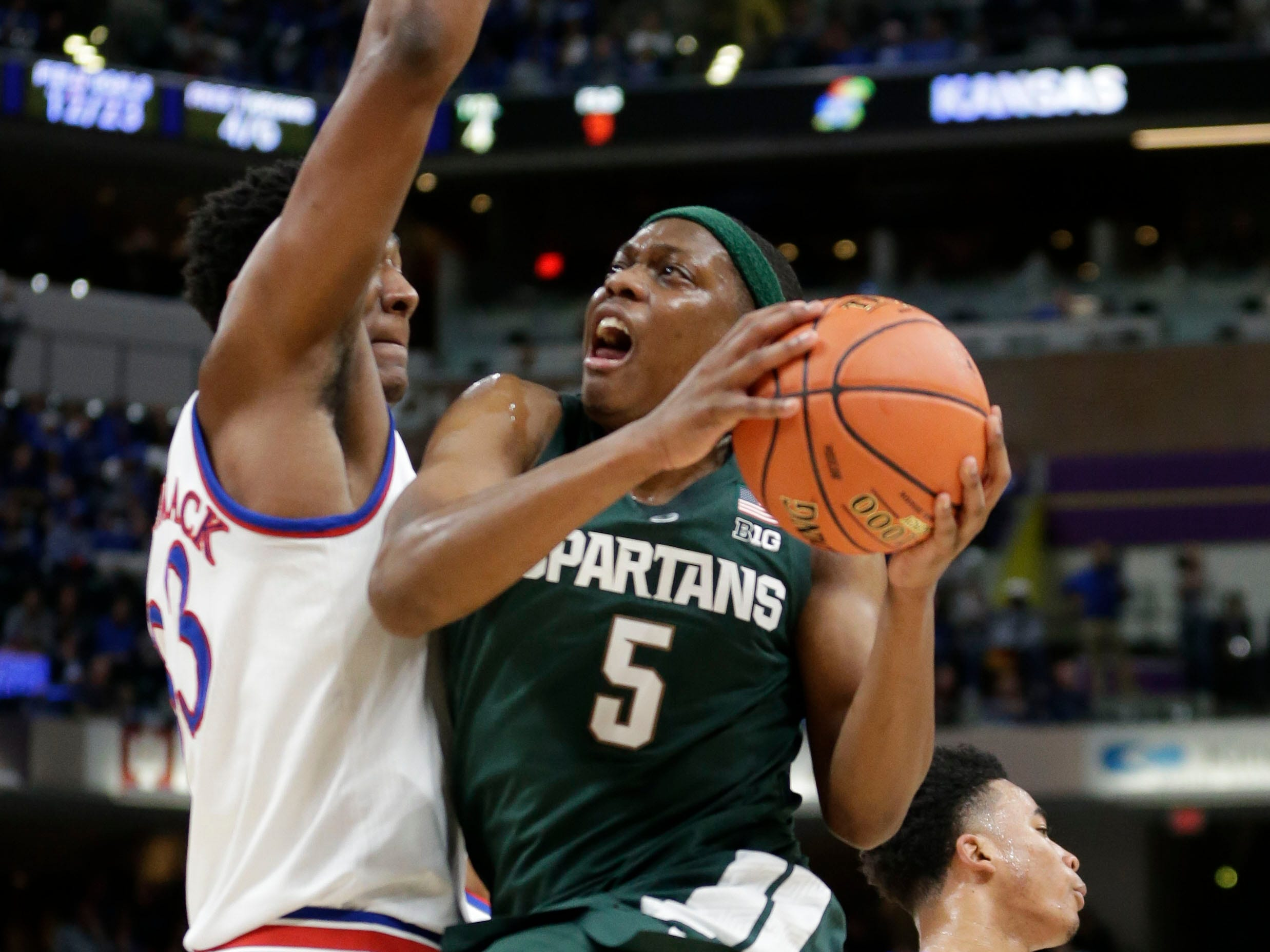 Michigan State guard Cassius Winston (5) tries to shoot around Kansas forward David McCormack (33) in the first half of an NCAA college basketball game at the Champions Classic in Indianapolis on Tuesday, Nov. 6, 2018.