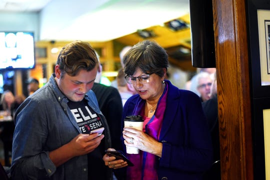 Democratic candidate for the 24th District state Senate seat Kelly Rossman-McKinney, right, and her finance director Nickolas Lentz check voting returns on their phones during a watch party on Tuesday, Nov. 6, 2018, at Frank's Press Box in Lansing.