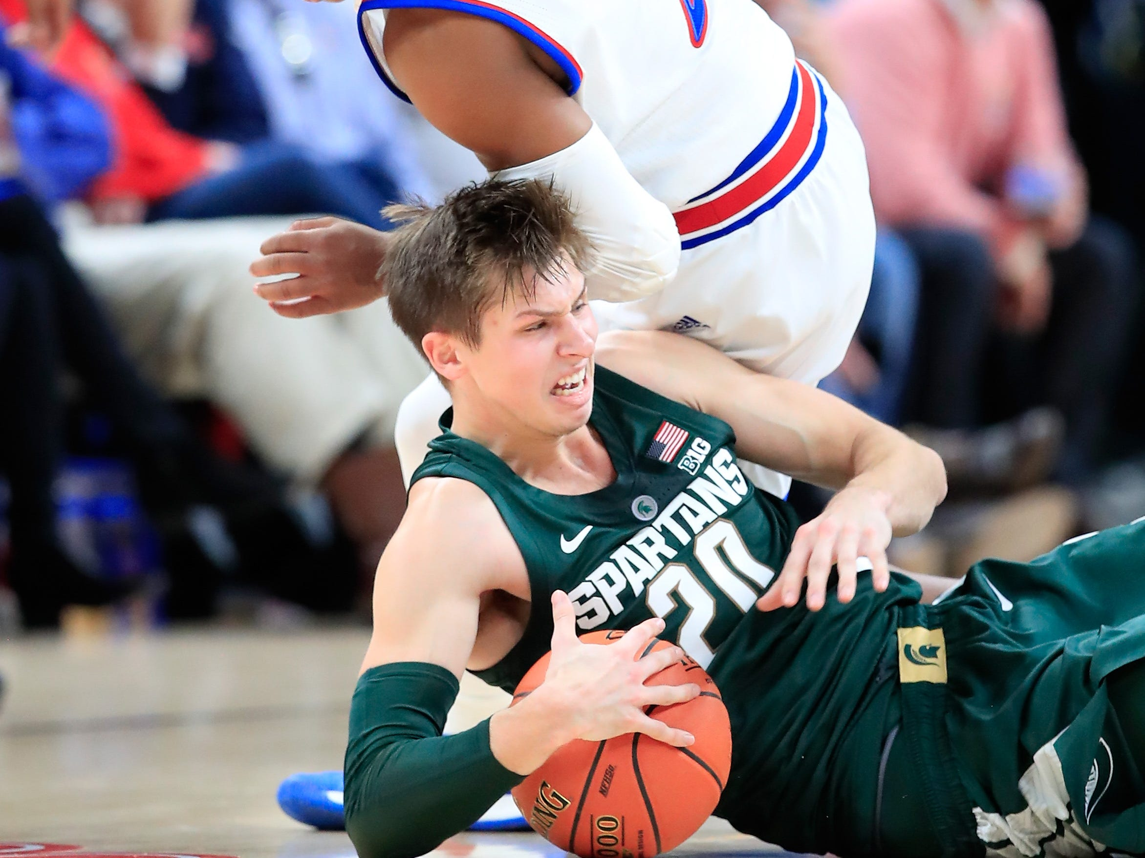Charlie Moore #2 of the Kansas Jayhawks and Matt McQuaid #20 of the Michigan State Spartans battle for a loose ball during the State Farm Champions Classic at Bankers Life Fieldhouse on November 6, 2018 in Indianapolis, Indiana.