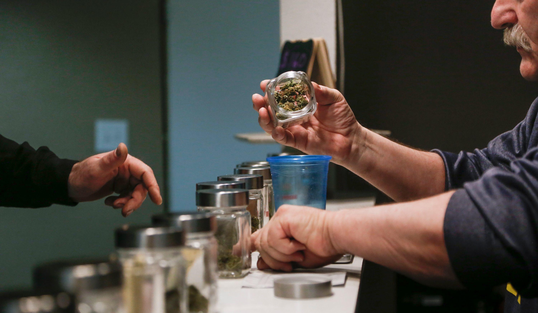 Stephen Joseph, owner of now closed medical marijuana dispensary Lansterdam, fills a customer's order May 2, 2017. [Photo by MATTHEW DAE SMITH | Lansing State Journal]