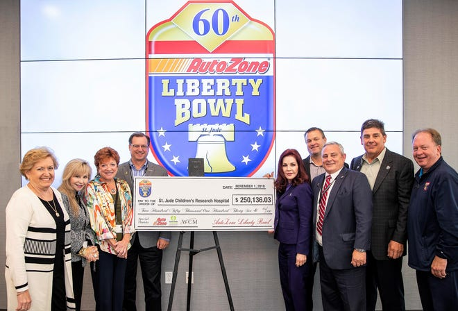 Kevin Nienhuis with ALSAC/St. Jude receives this year's contribution from AutoZone Liberty Bowl officers, committee members and Priscilla Presley. From left are Patti Shannon, Leigh Shockey, Pat Caldwell, Bill Giles, Presley, Nienhuis, Bill Kinkade, Chris Moore and David Boston.