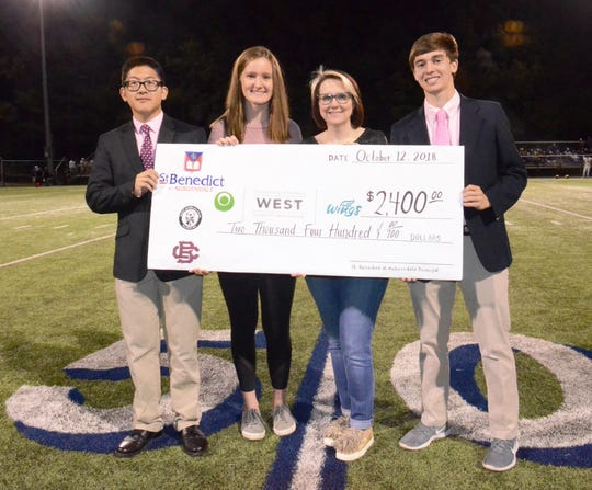 From left, St. Benedict SGA President Matthew Li, Secretary of the St. Agnes SGA Sarah Wray, WINGS Support Services Manager of Public Relations and Special Events Keri Burnette and Christian Brothers Leadership Council President Gerard Tavoletti pose with the commemorative check for $2,400.