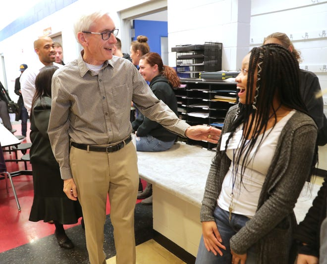 Gov.-elect Tony Evers is considering ending a newpolicy that will requiresome people to work to receive health insurance through the state's BadgerCare Plus program. Here, he talks with Boys & Girls Club assistant teacher Lisa Simmons as he visits the Boys & Girls Club.