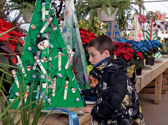 Elijah Abram, 7, of Vernon cast his vote for a tree made by Brownie Troop 4801 for best of show in the Festival of Trees during Midnight Magic on Dec. 7 at the Garden Mart.