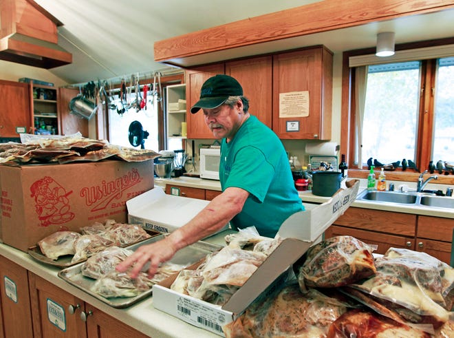 Former restaurant chef Steve Paradowski unpacks food that was donated for an Oktoberfest meal at Kathy's House.
