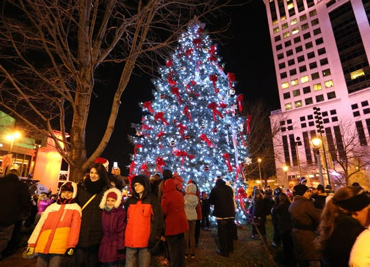 People pose for pictures during Milwaukee's 102nd Christmas tree lighting ceremony at Red Arrow Park.