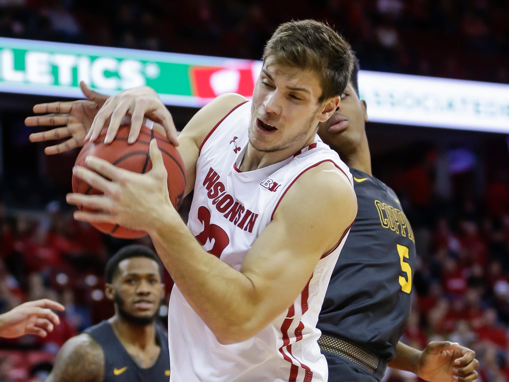 Wisconsin's Ethan Happ, left, grabs an offensive rebound against Coppin State's Cedric Council.