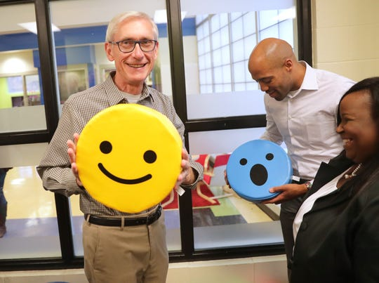 Gov.-elect Tony Evers jokingly holds a smiley emoji pillow to reflect how he's feeling after winning the election.