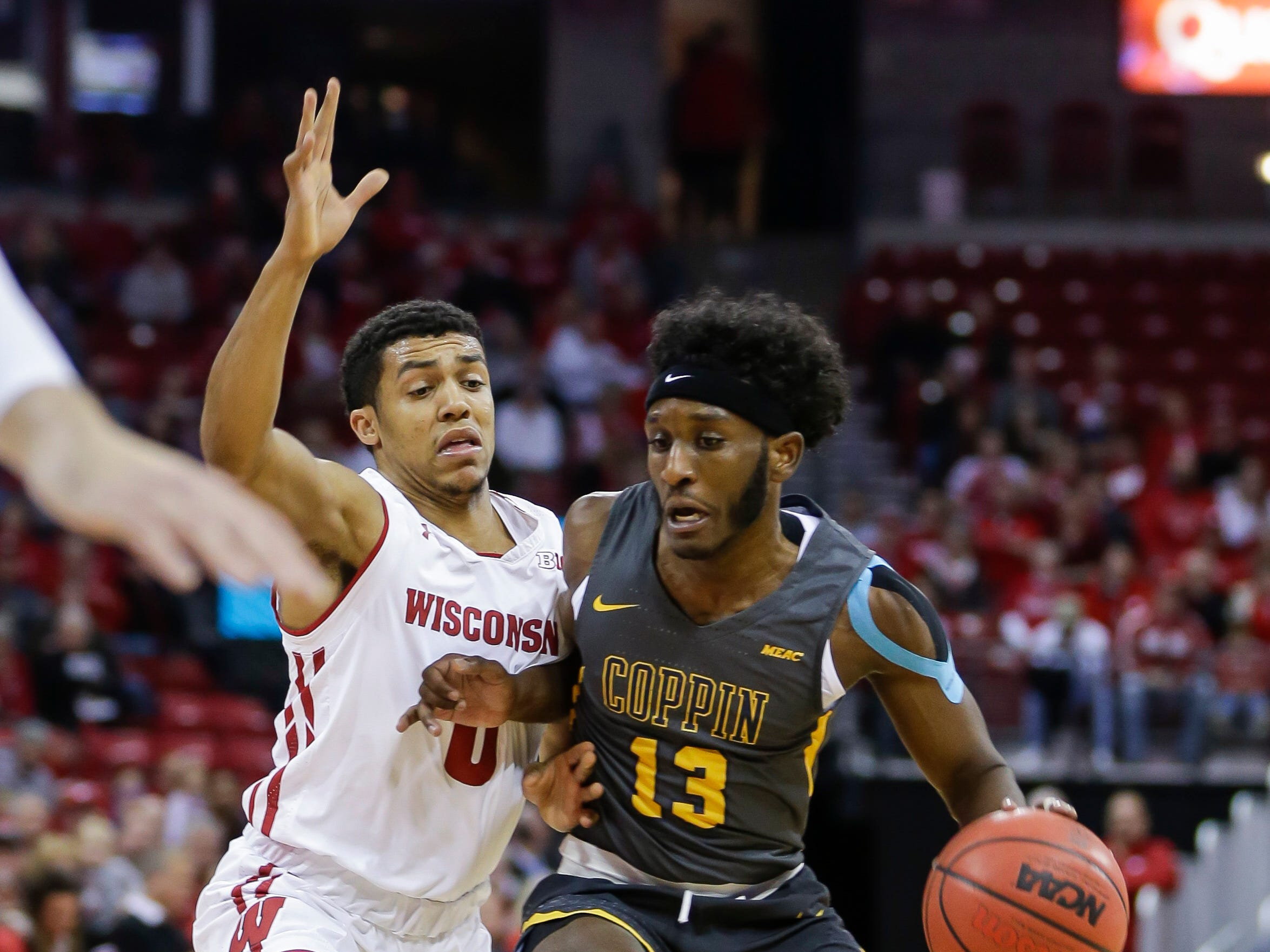 Coppin State's Dejuan Clayton drives on Wisconsin's D'Mitrik Trice.